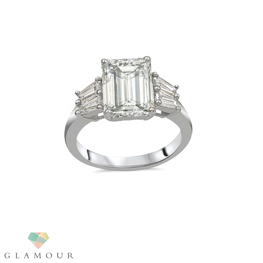 Three Stone Emerald cut Diamond Ring Make a outstanding statement with our Emerald cut three stone diamond made from 18k white gold featuring Emerald cut Diamond at the center in a prong setting making it ideal for all occasions.